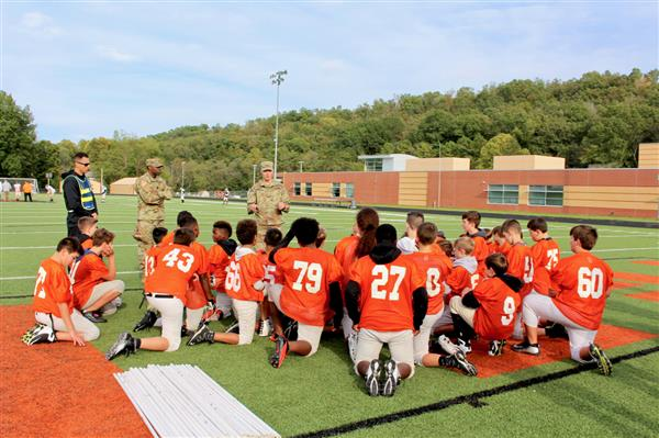 7th grade football players learn team-building plays