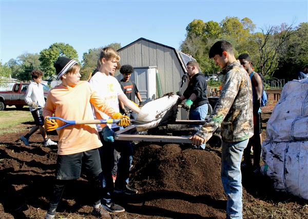 Football, soccer players prepare community garden for winter